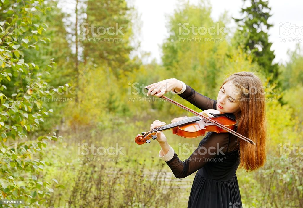 Girl with violin in the forest stock photo