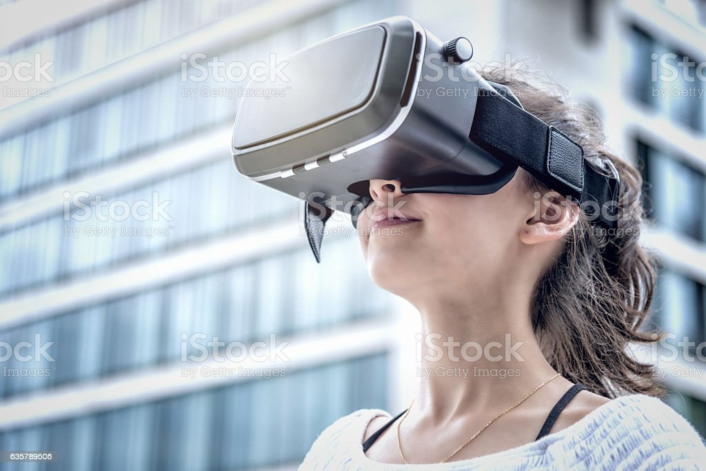 girl with virtual reality simulator in modern city stock photo