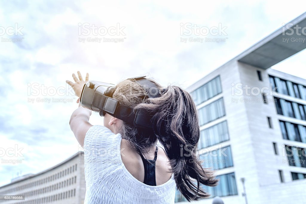 girl with virtual reality simulator orientating in city stock photo