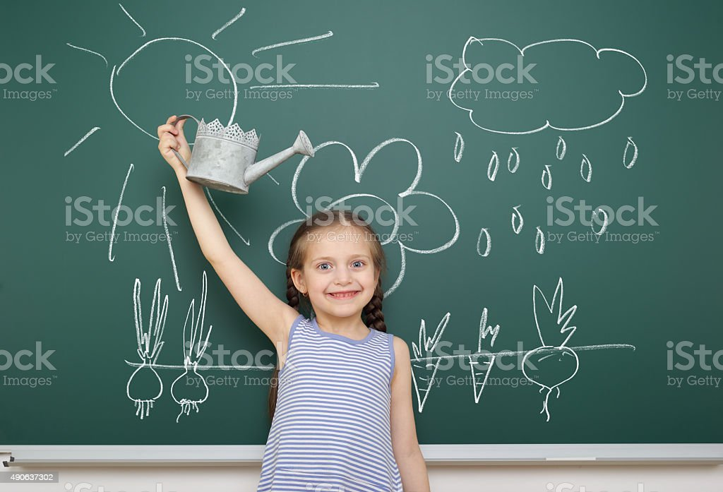 girl with watering can drawing on school board stock photo