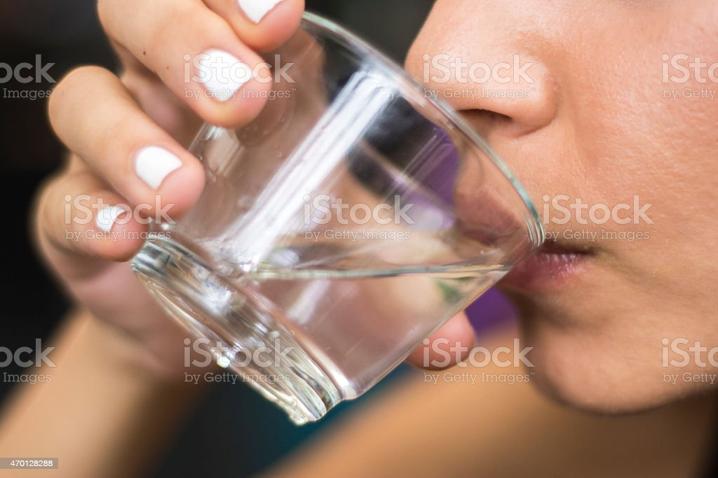 A girl with white nail polish drinking water from a glass stock photo