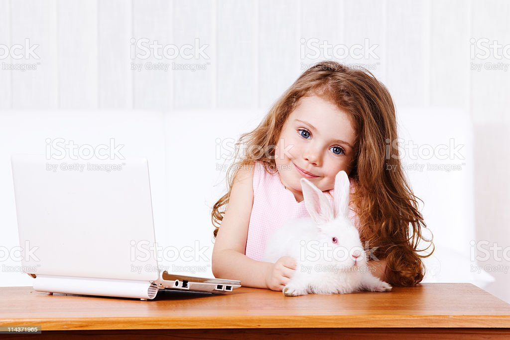 Girl with white rabbit and laptop stock photo