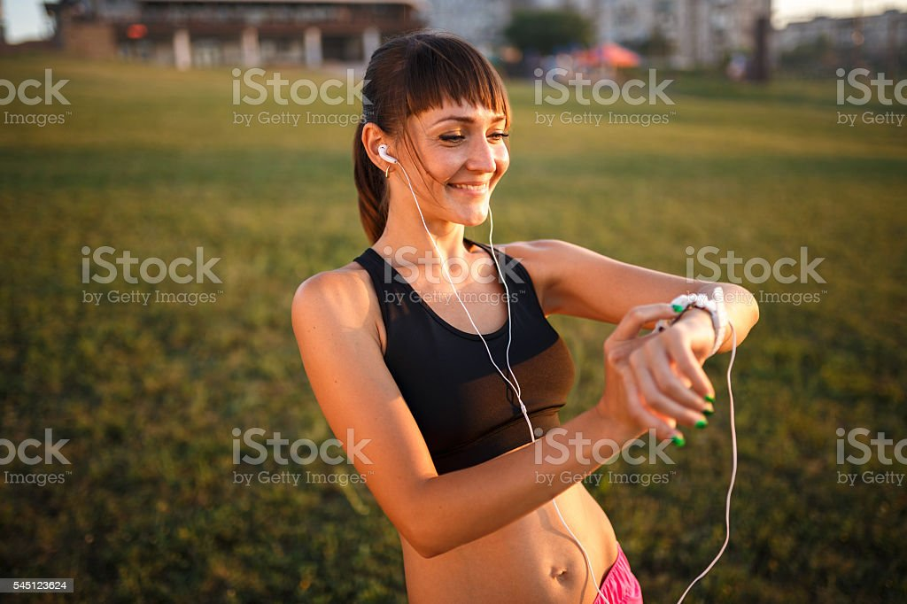 girl with wrist fitness bracelet outdoors stock photo
