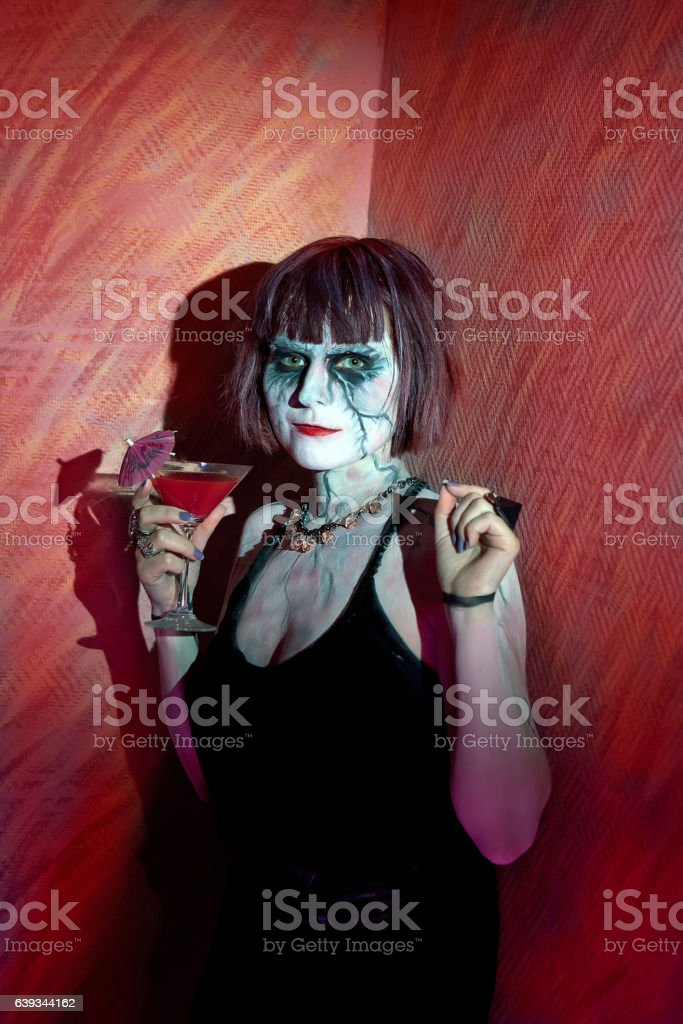 girl with zombie makeup with glass of red cocktail stock photo
