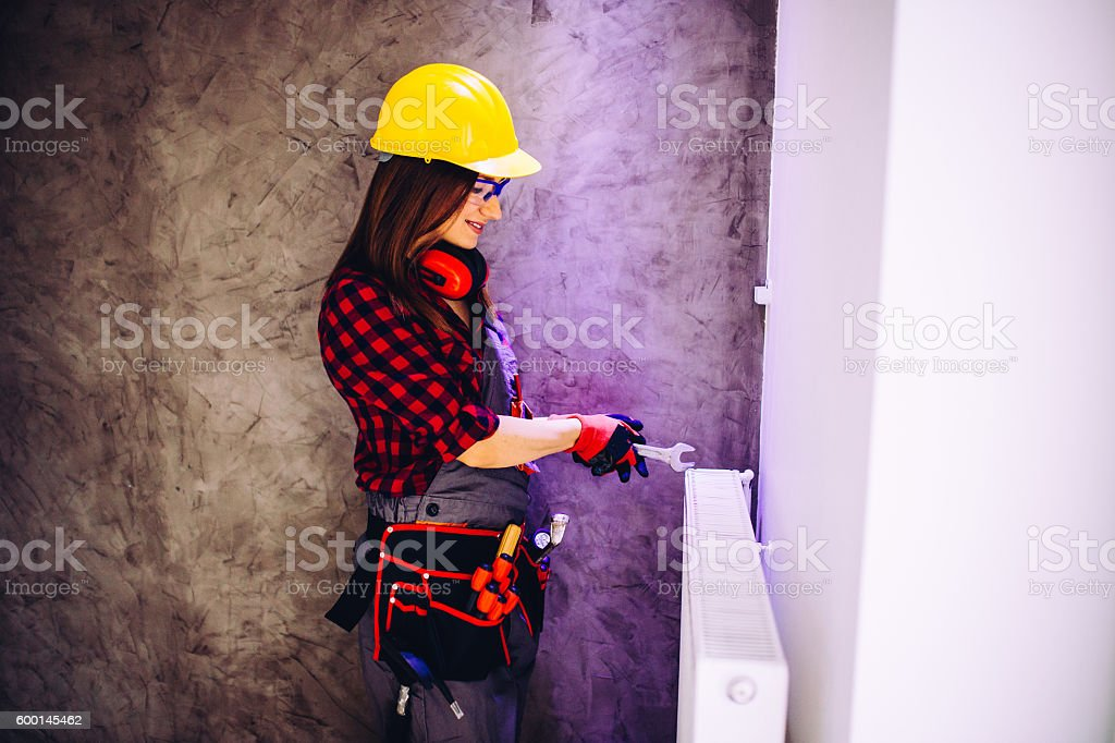Home Improvement woman wearing hard hat is working indoors by the...