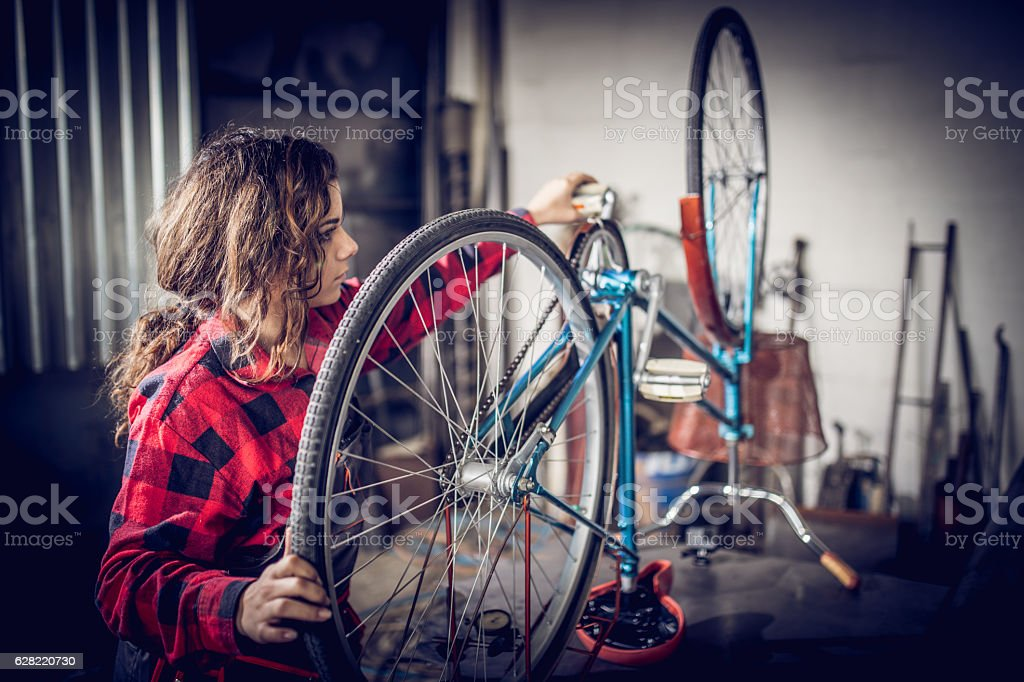 Girl working on her bicycle stock photo
