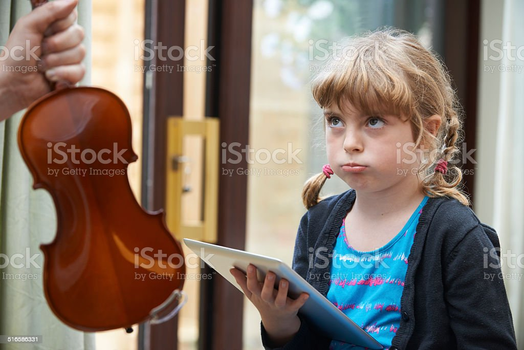 Girl Would Rather Play On Digital Tablet Than Practise Vio stock photo