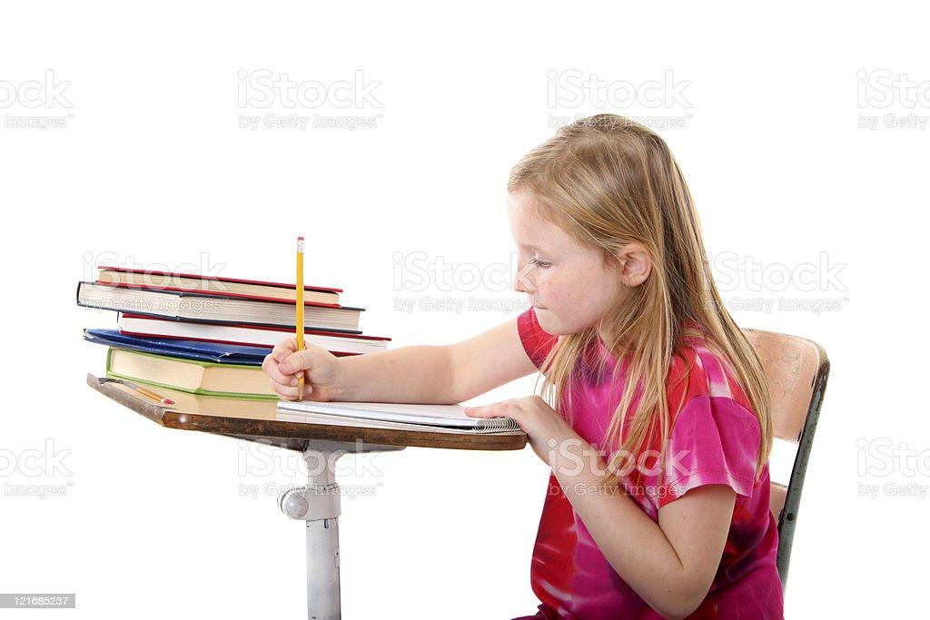 girl writing at school desk stock photo