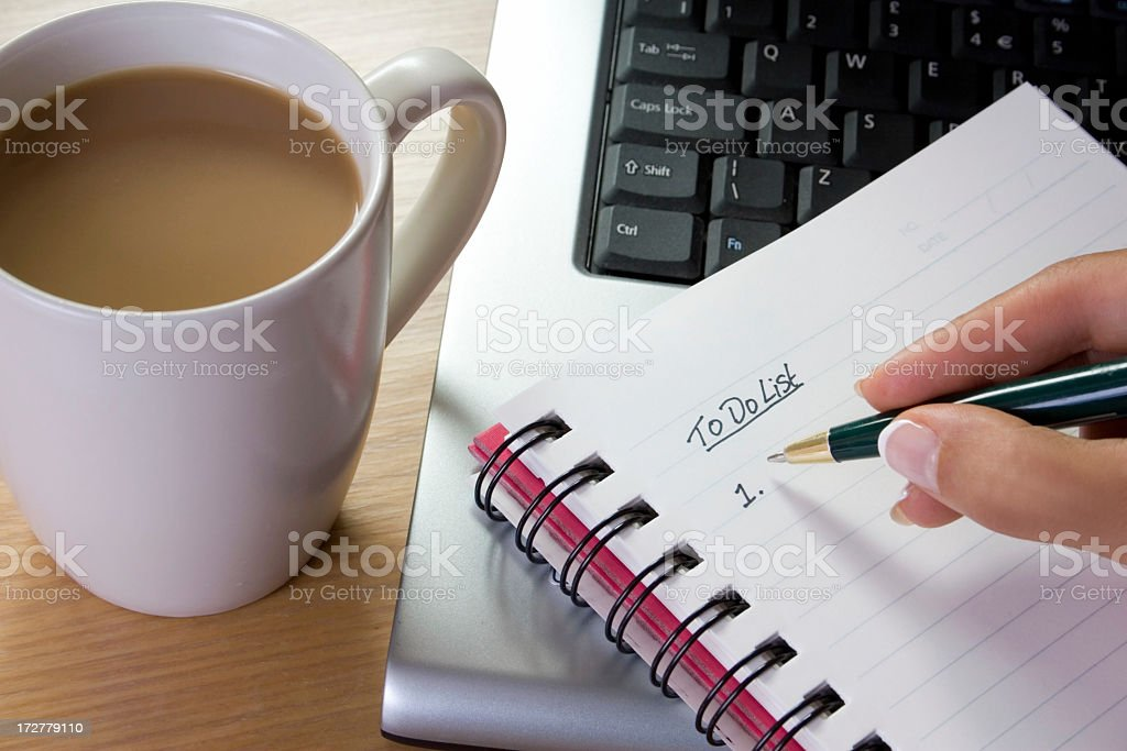 A girl writing her to do list in her notebook stock photo