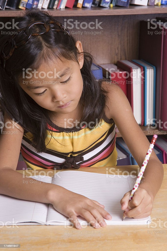 Girl writing in composition book (part of homework series) royalty-free stock photo