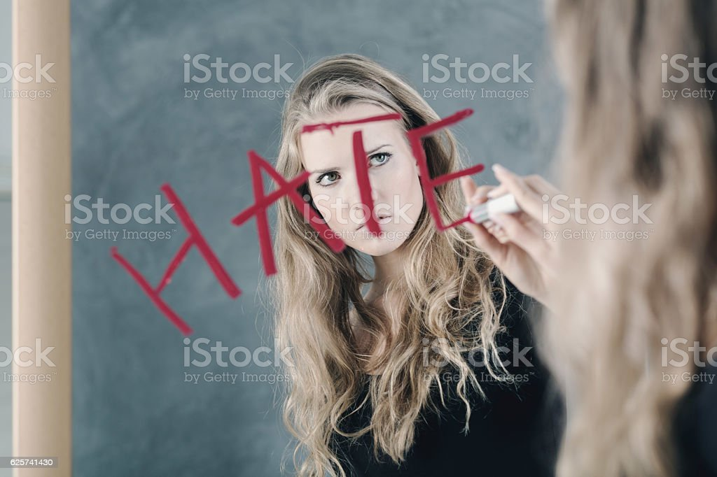 Girl writing word 'hate' stock photo
