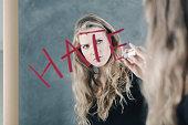 Girl writing word 'hate'