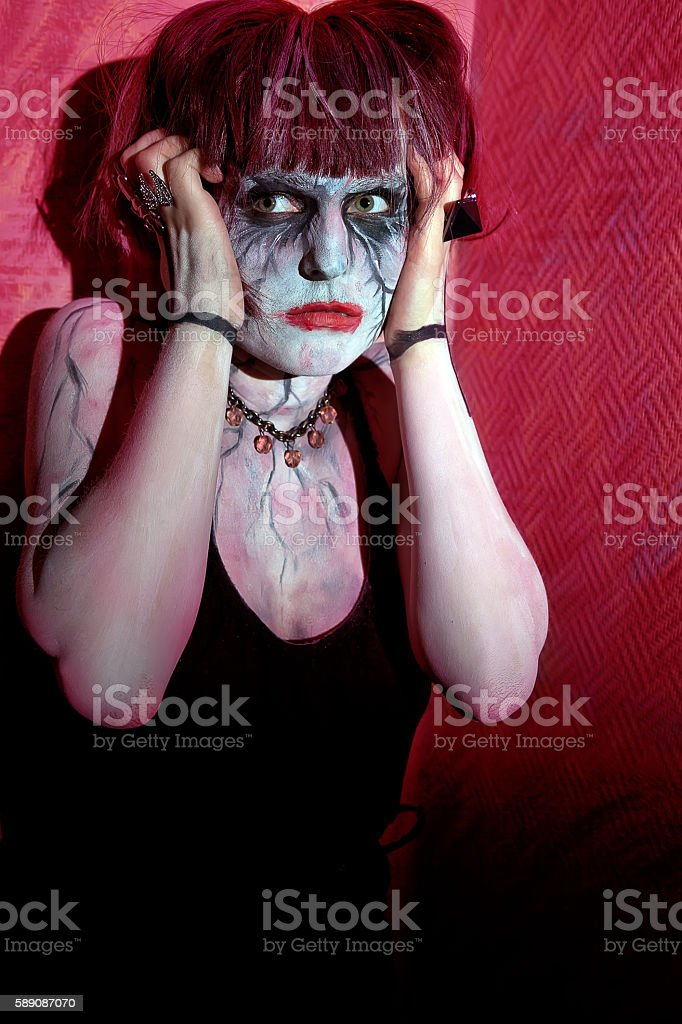 girl zombie horror against red wall stock photo
