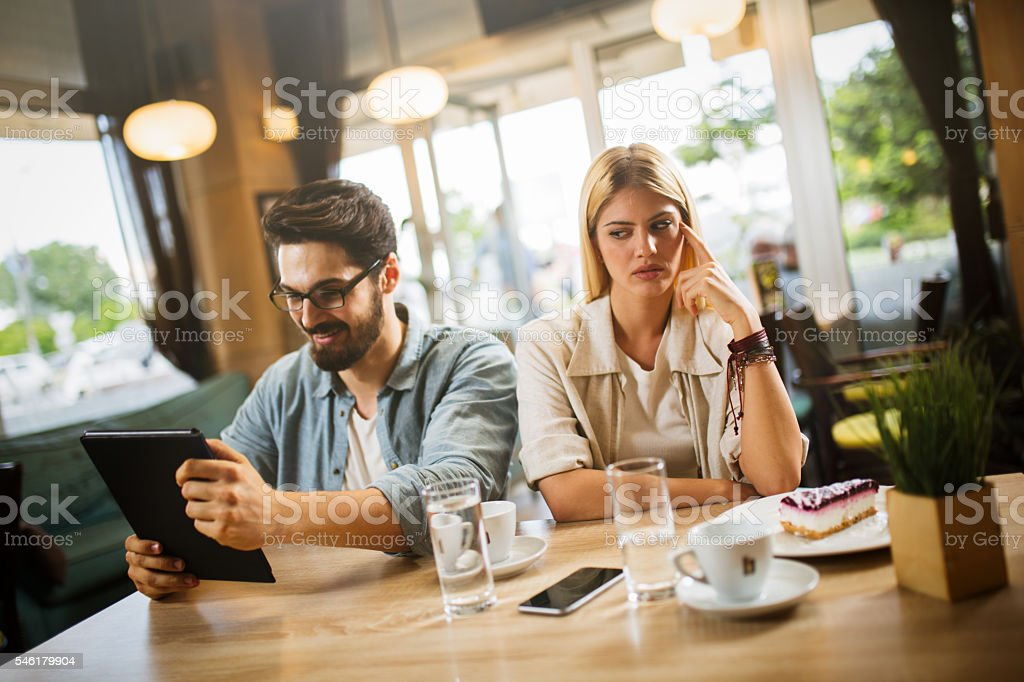 Girlfriend annoyed with boyfriend using digital tablet on date. stock photo
