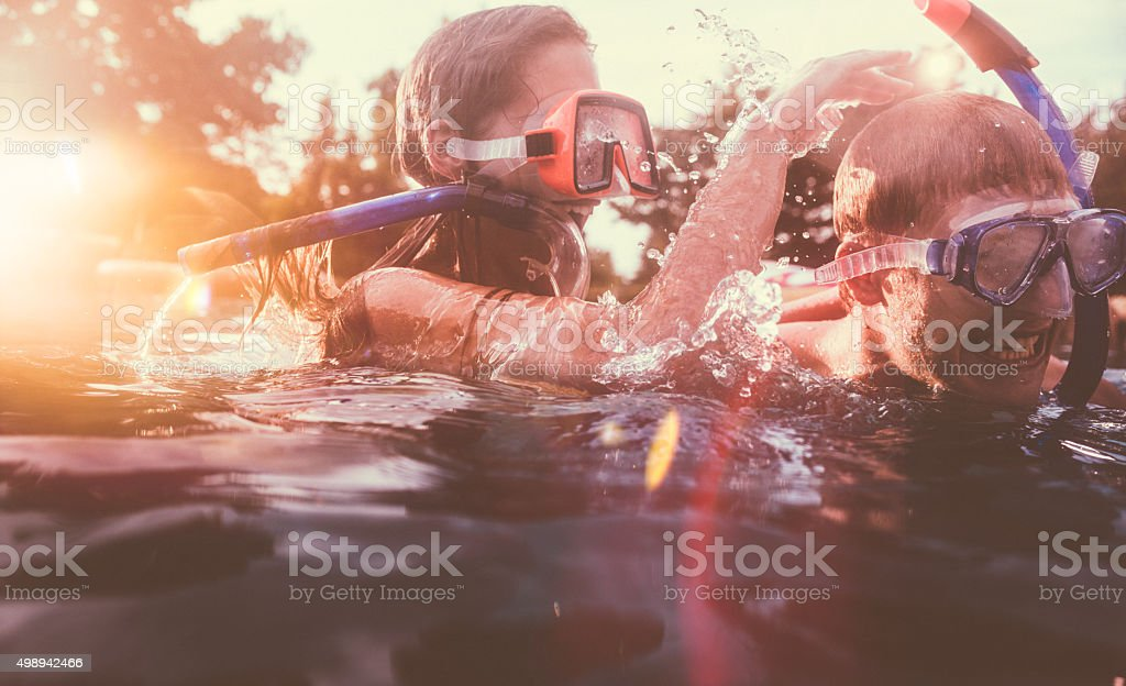 Girlfriend playfully trying to dunk boyfriend in pool with snorkels stock photo