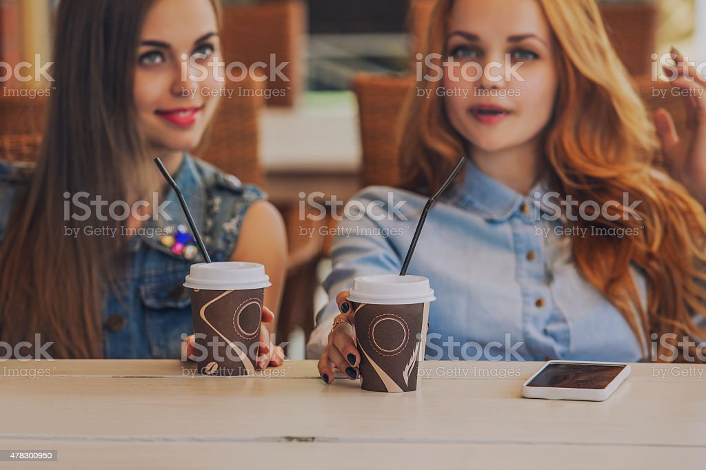 Girlfriend women in a summer cafe with cups of coffee stock photo