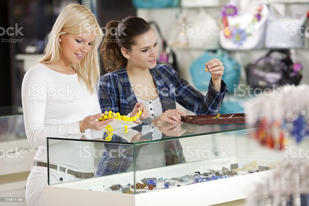 girlfriends are buying fashion accessories bracelets, necklaces in departmant store royalty-free stock photo