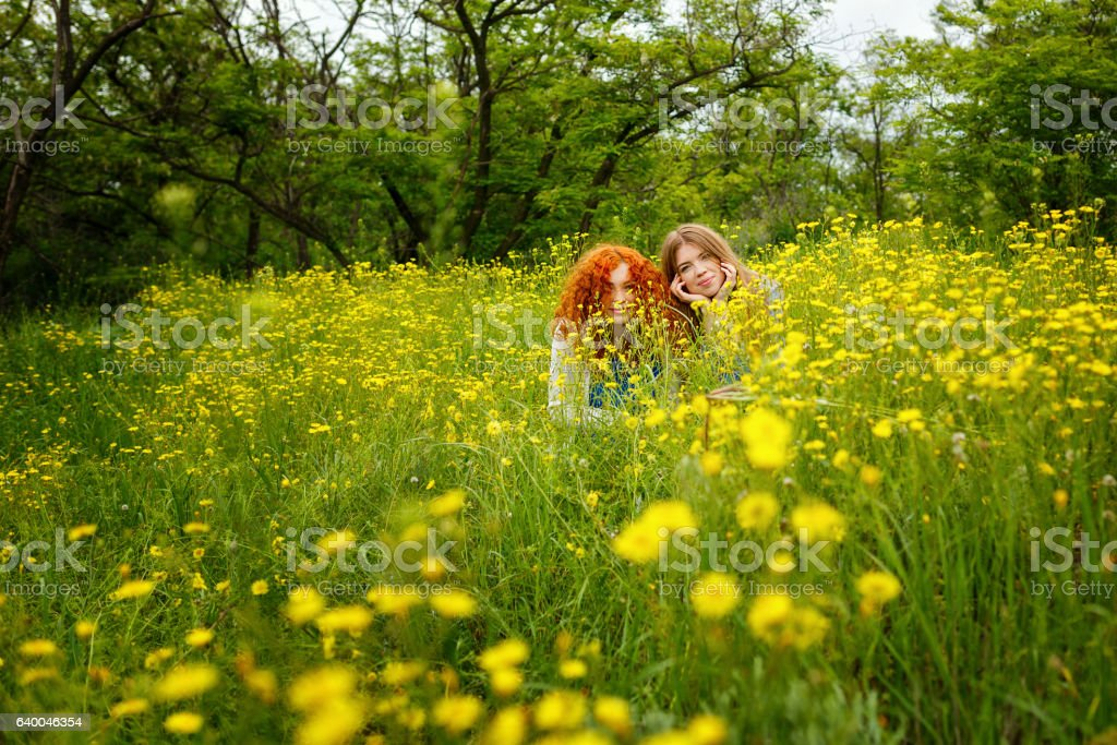Girlfriends are hiding in flowers stock photo