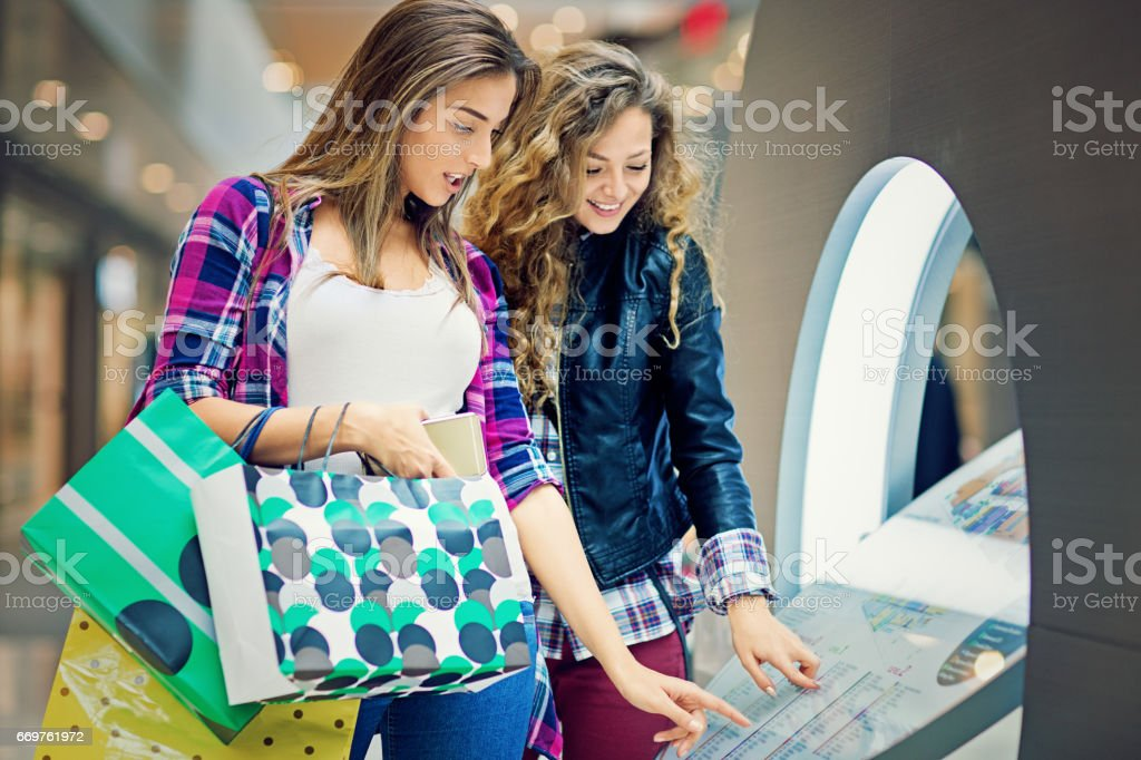 Girlfriends are looking store directory in the Mall stock photo