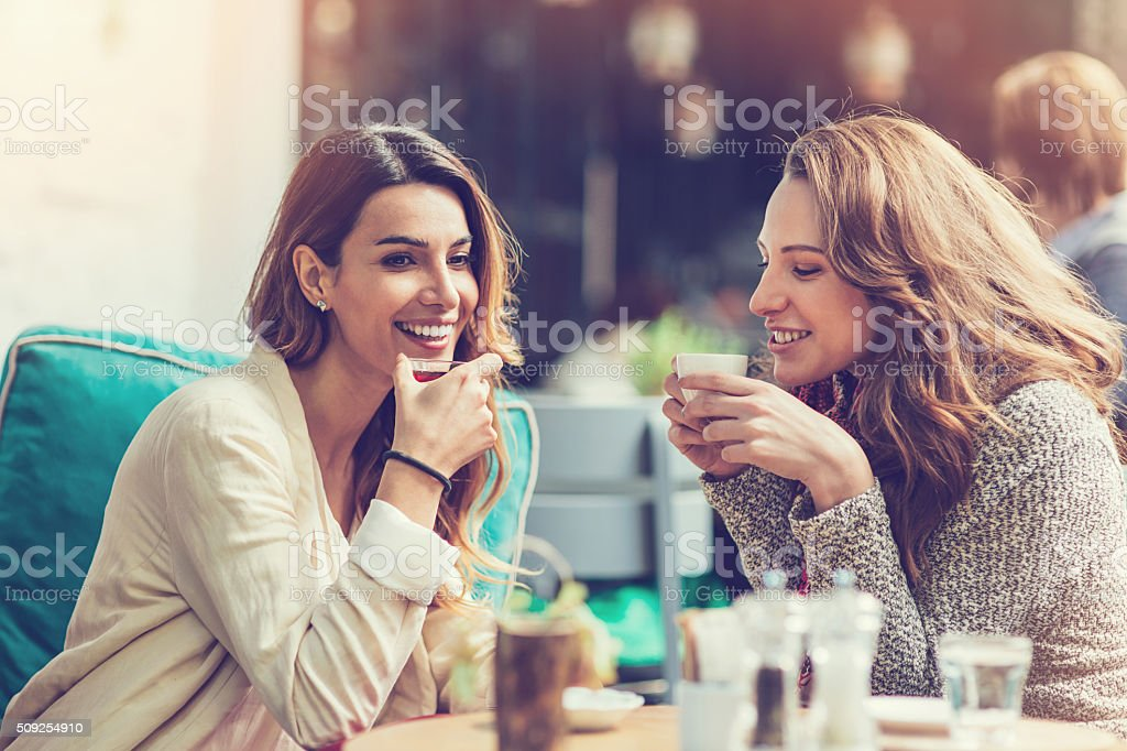 Girlfriends chatting and having coffee stock photo