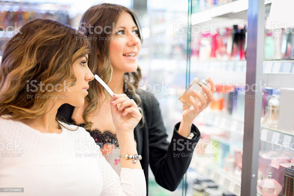 Girlfriends choosing perfume stock photo