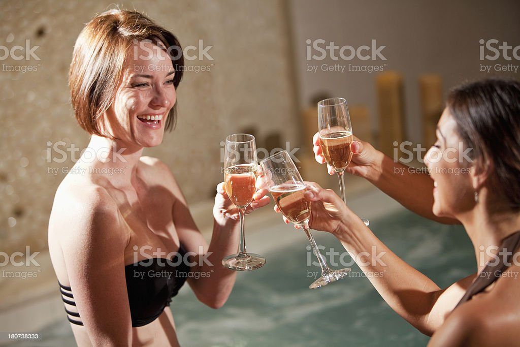 Cropped view of three mature women celebrating, drinking champagne in...