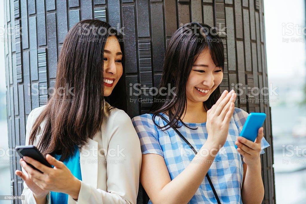 Girlfriends having fun with smart phones stock photo
