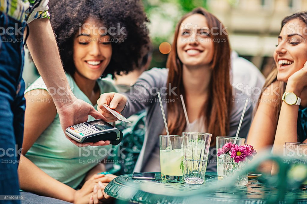 Girlfriends in cafe making payment stock photo