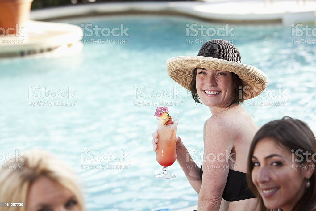 Girlfriends relaxing by pool with drinks royalty-free stock photo