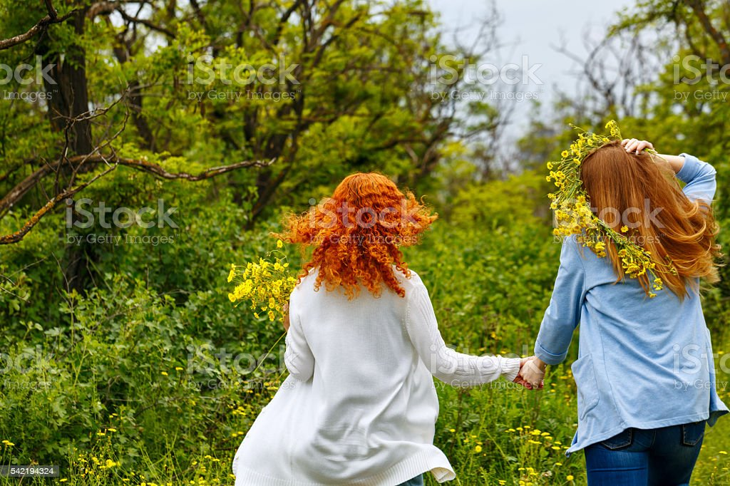 Girlfriends stroll hand in hand. stock photo