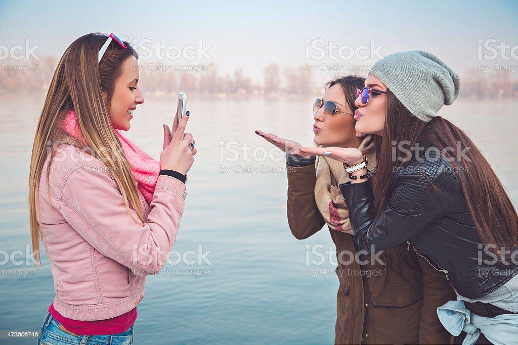 Girlfriends taking a photo of them sending kiss stock photo