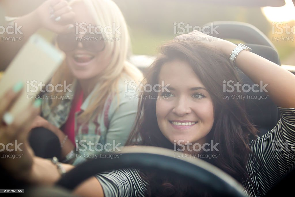 Girlfriends taking selfie in car stock photo
