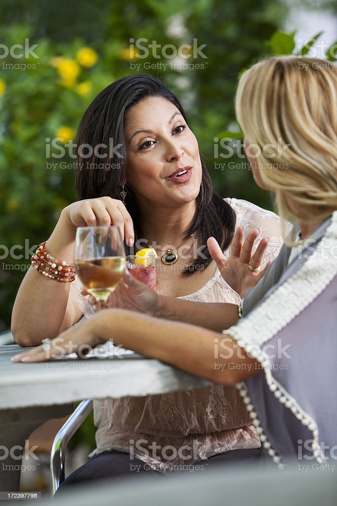Girlfriends talking and drinking outdoors royalty-free stock photo