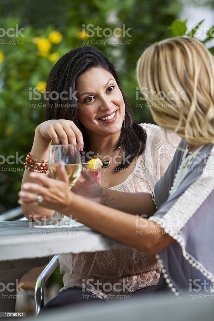 Girlfriends talking and drinking outdoors stock photo