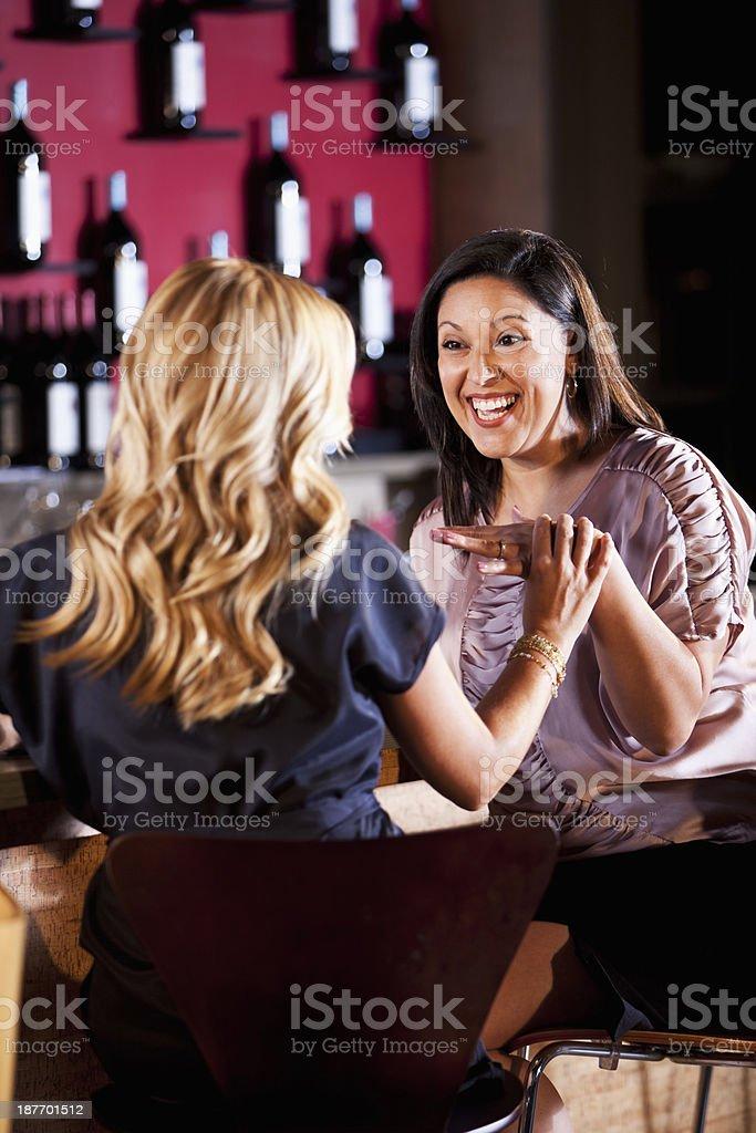 Girlfriends talking at bar stock photo