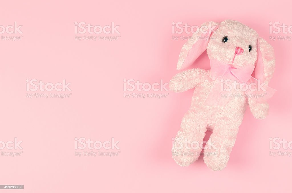 girlish soft toy on a pink gentle background stock photo