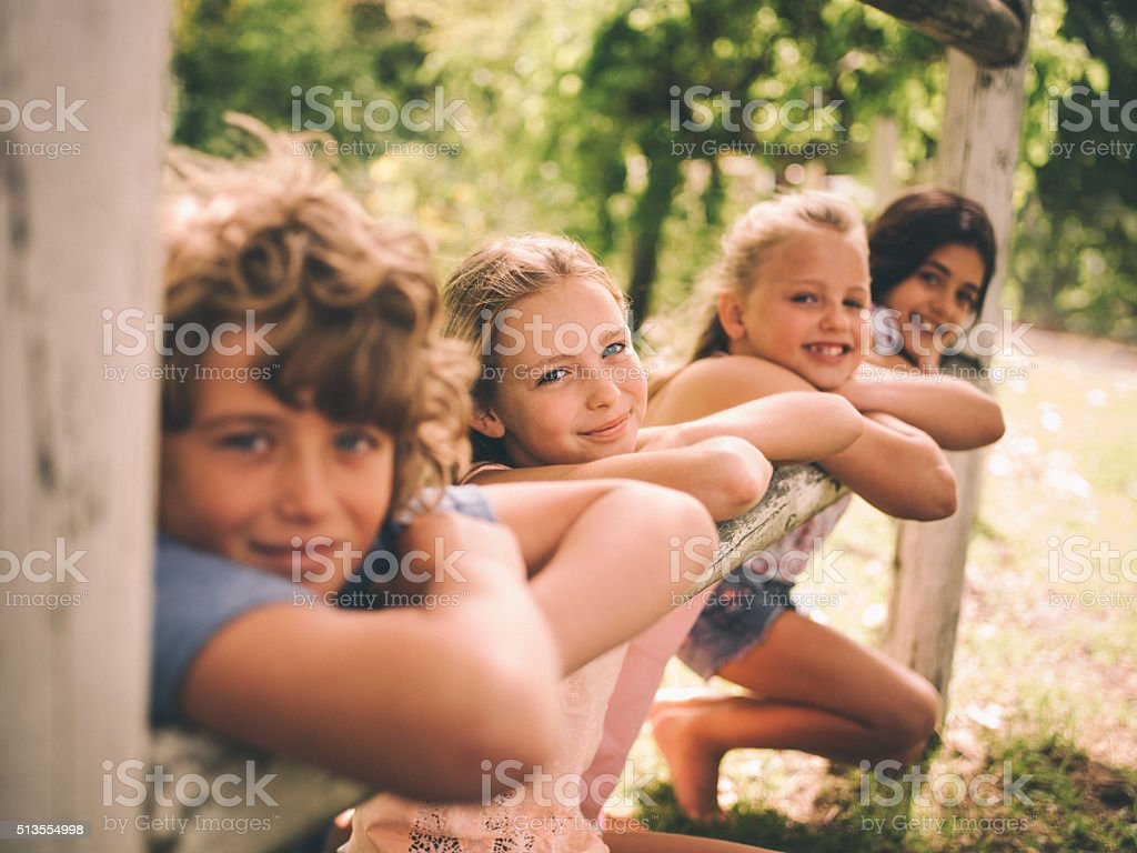 Girls and boy leaning on wooden fence on summer day stock photo