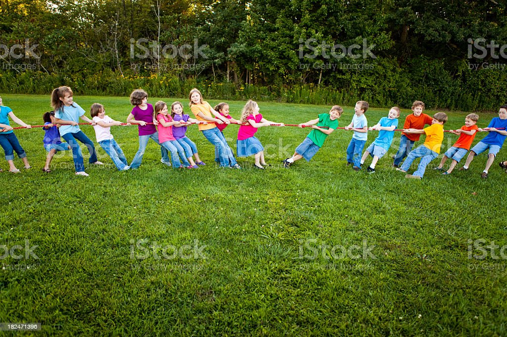 Girls and boys playing tug-of-war outside royalty-free stock photo