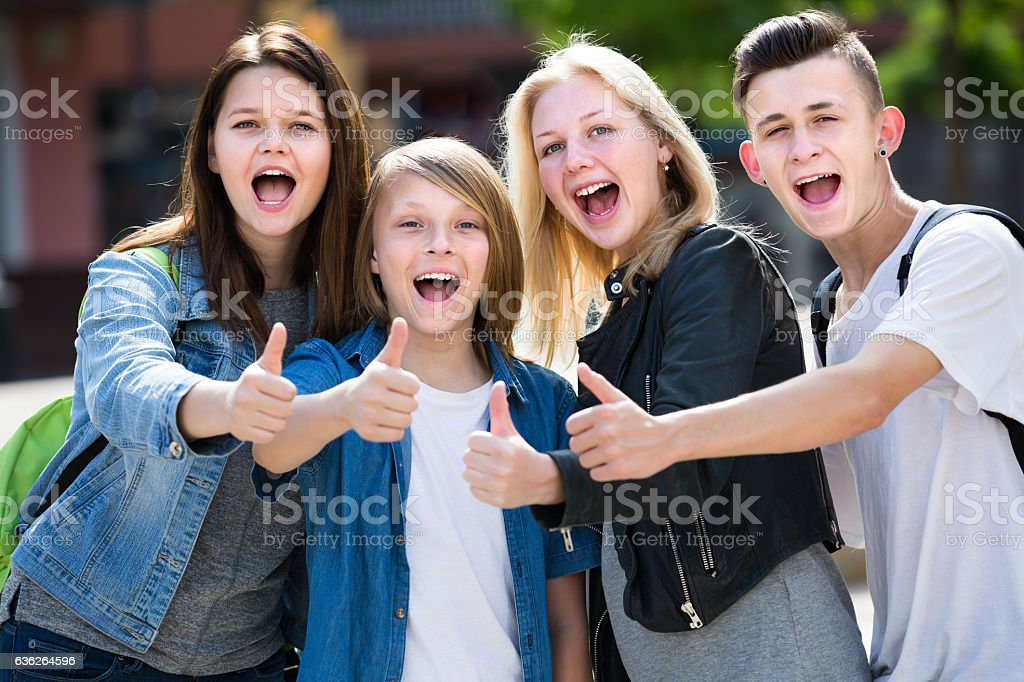Girls and boys posing with thumbs up stock photo
