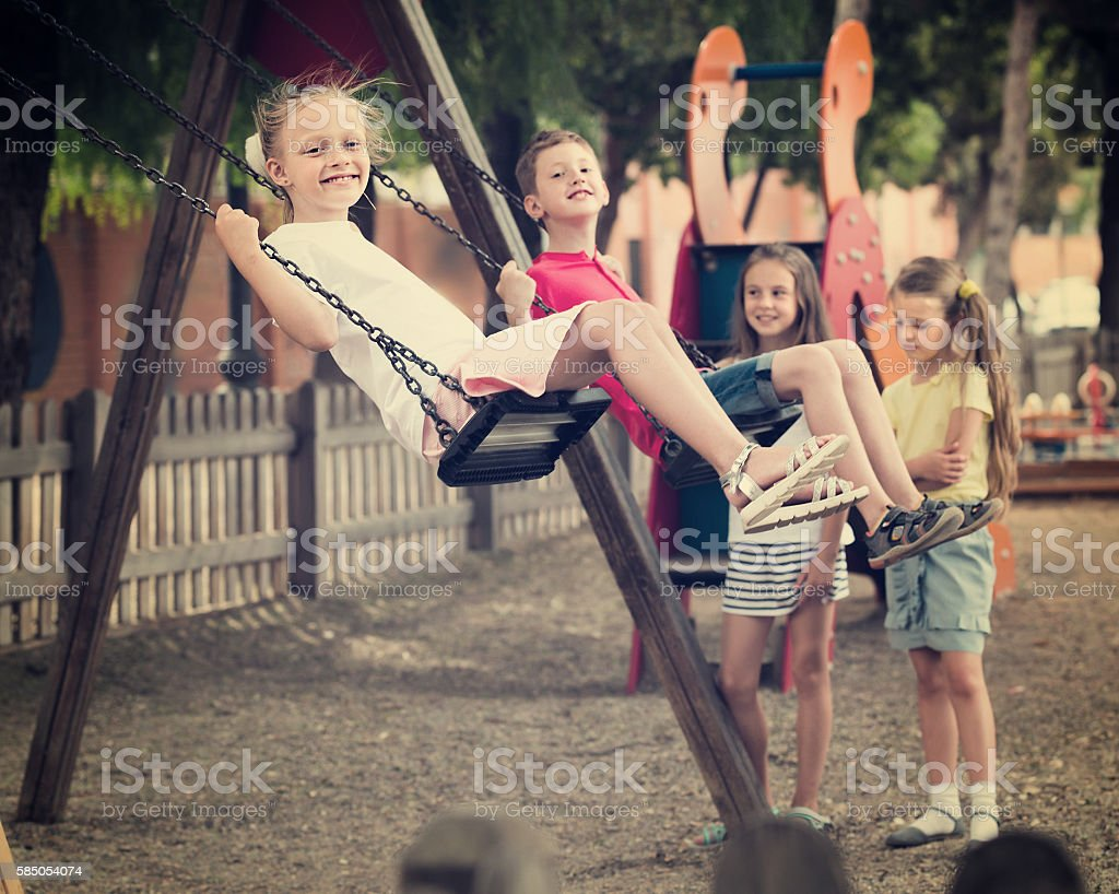 Girls and boys swinging on playground stock photo