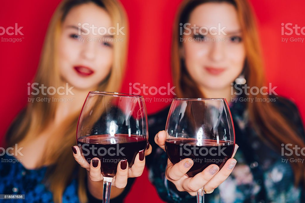 Girls and glasses of red wine stock photo
