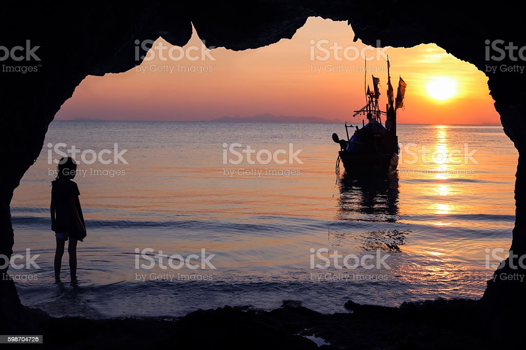 Girls and local boats with sunset in Thailand. stock photo