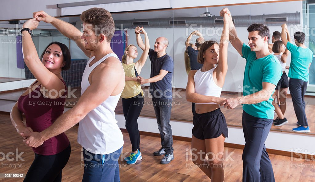 girls and men learning salsa stock photo