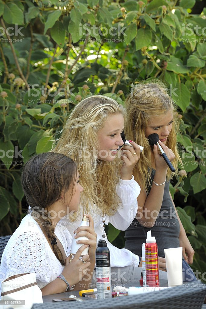 girls applying makeup in garden royalty-free stock photo