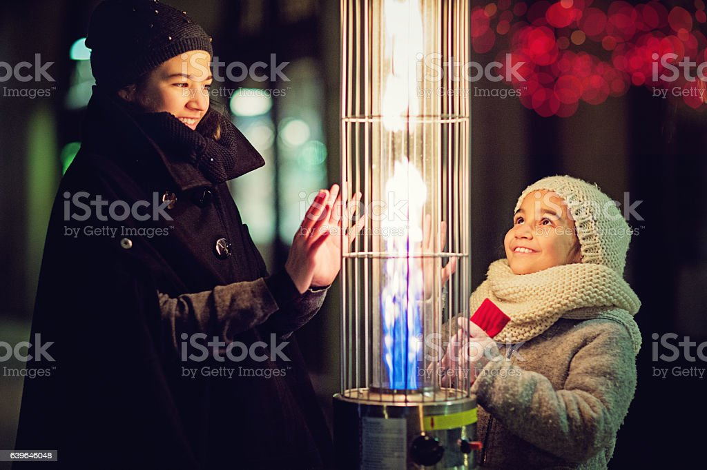 Girls are warming their hands on the gas heater stock photo