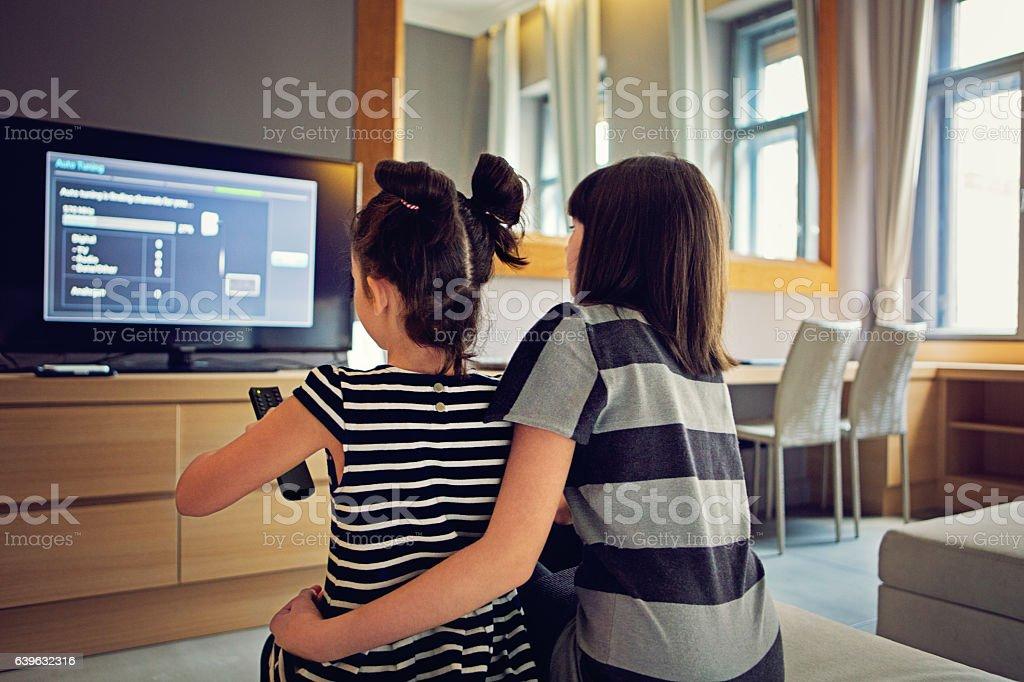 Girls are watching TV stock photo