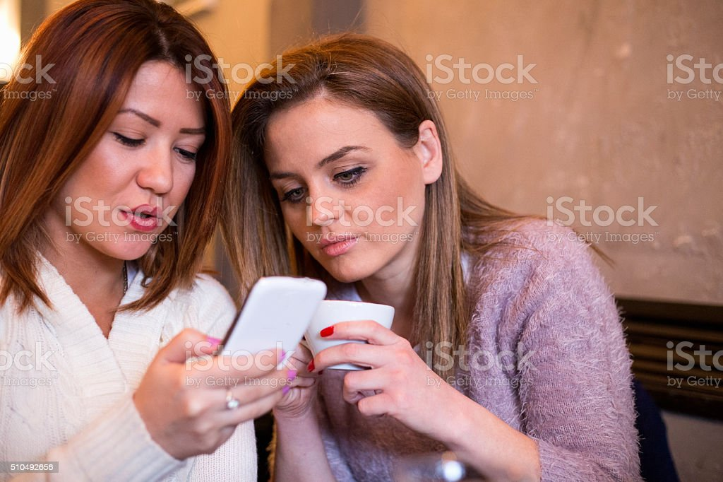 Girls at cafe surfing the net stock photo
