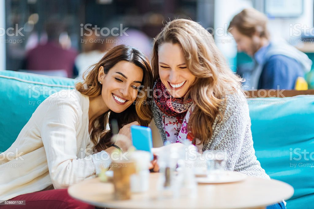 Girls at cafe text messaging on smartphone stock photo