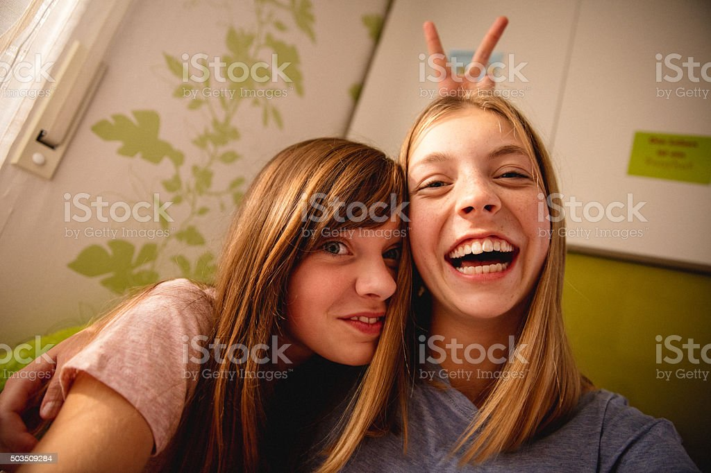 Girls being silly in colourful bedroom while posing for camera stock photo