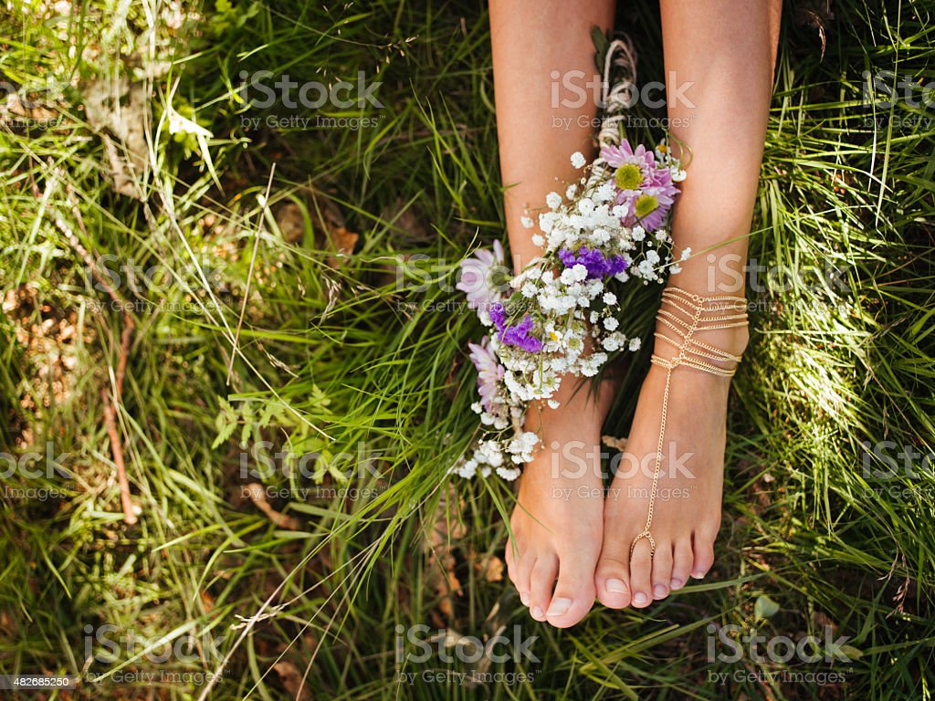 Girl's bejewelled feet in green grass with flowers stock photo